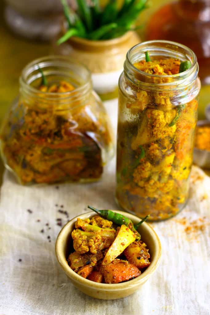 side shot of Punjabi mixed vegetable pickle in a ceramic bowl and glass jars