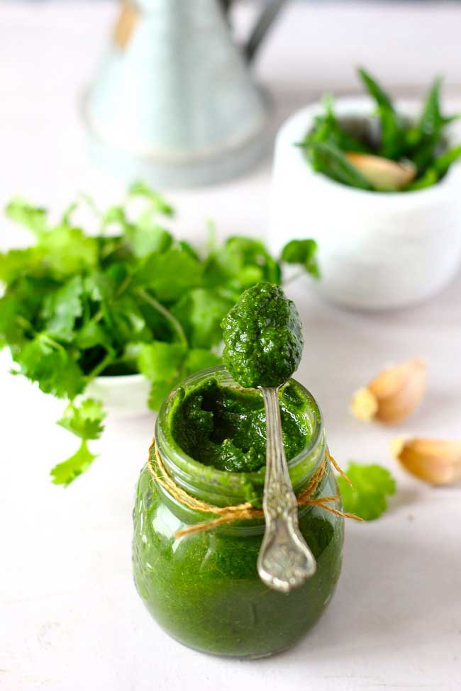 Mint Chutney in a glass bottle with a spoonful of chutney on top.