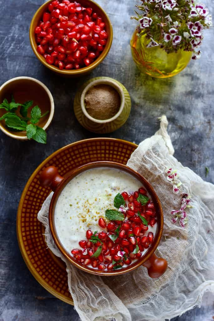 Mint and Pomegranate Raita is a delicious combination of mint, coriander, and pomegranate pearls.