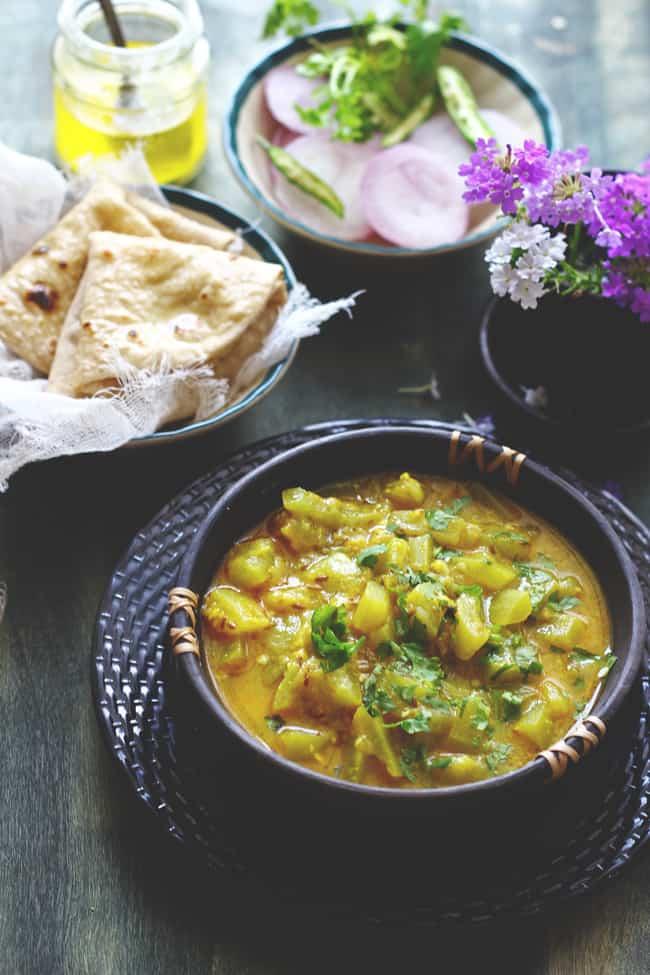 Side shot of dahi lauki in a black serving bowl.