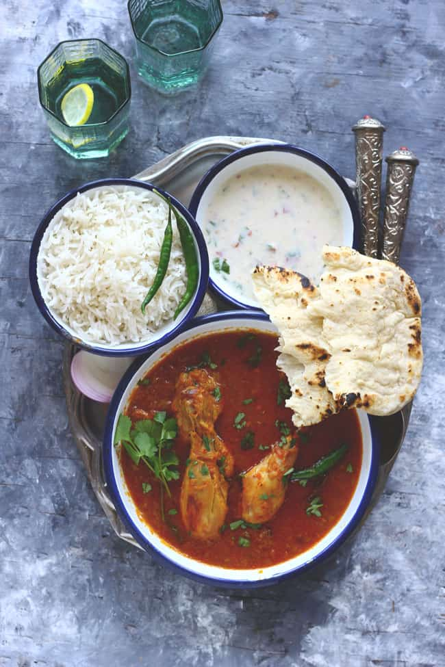 aerial shot of chicken curry with basmati rice, naan. and raita on a plate