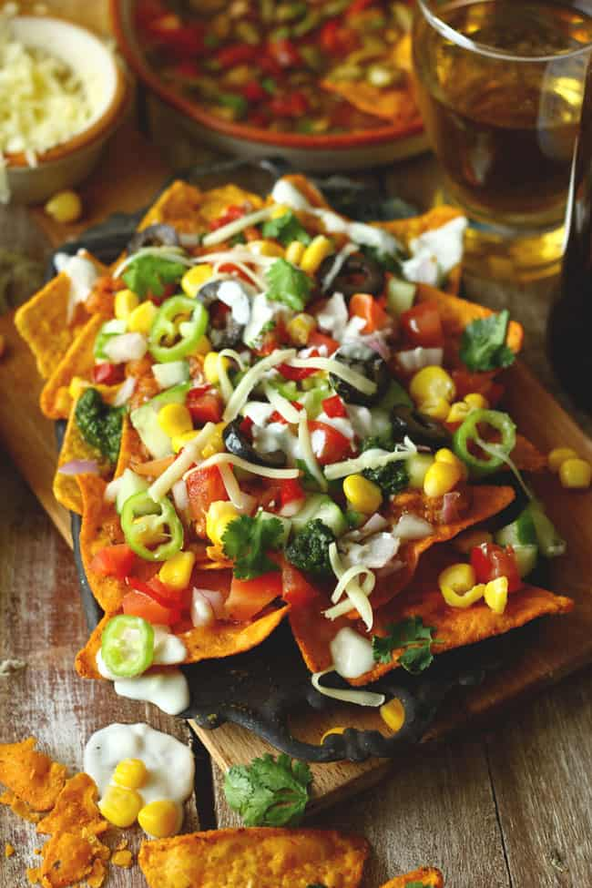 These loaded vegetarian nachos are laced with locally available ingredients and Indian flavors. Find loaded vegetarian nachos recipe