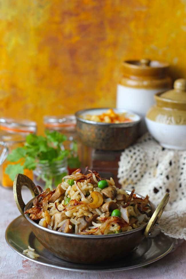 Side shot of mushroom pulao in a copper serveware.