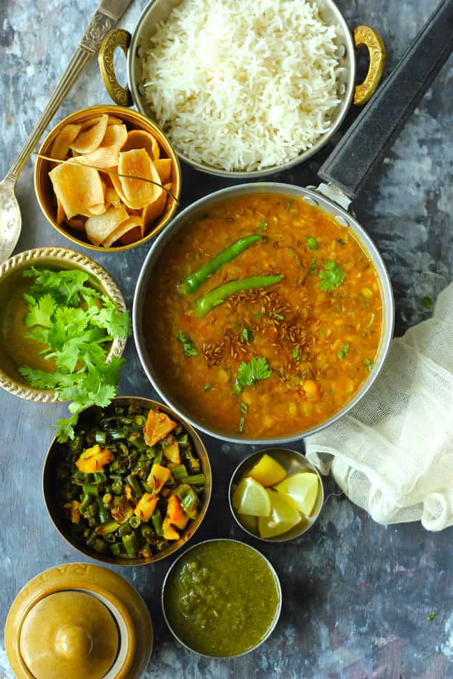 Aerial shot of Indian meal of dal, rice, papad, green beans potato sabzi