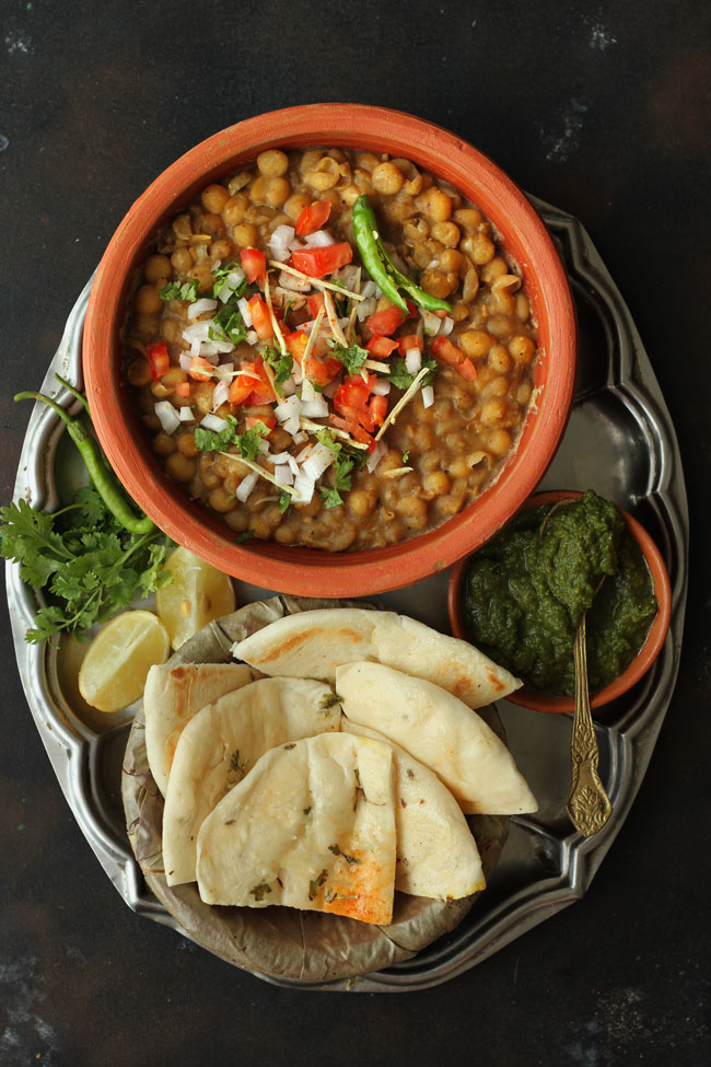 Aerial shot of matar and kulcha in a stainless steel plate.