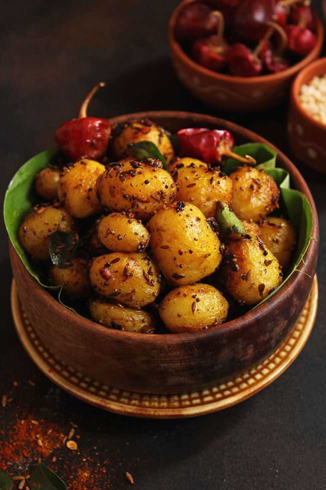 side close up shot of masala potato roast in a wooden bowl