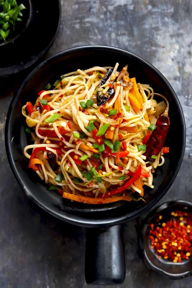 aerial shot of chilli garlic noodles in a black serving bowl