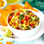 side shot of corn salsa in a white ceramic bowl