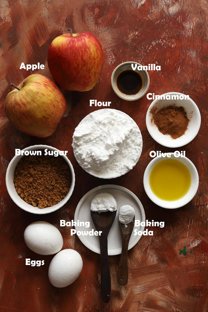 Ingredients - flour, brown sugar, apples, eggs, olive oil, cinnamon powder, baking soda, baking powder for apple muffins.