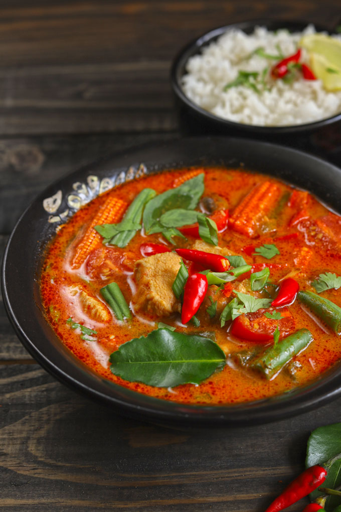 Thai Red Chicken Curry Garnished With Red Chilli And Kaffir Lime Leaves In A Black Bowl