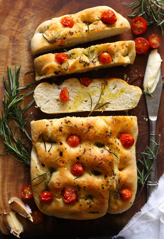 Slices of focaccia bread topped with cherry tomatoes, rosemary and olive oil on a wooden board, with garlic and rosemary beside.