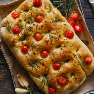 Focaccia bread topped with cherry tomatoes, rosemary and olive oil on cloth, with garlic beside