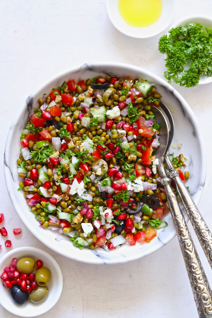 Lentil Salad in a white bowl with serving spoons on a white table