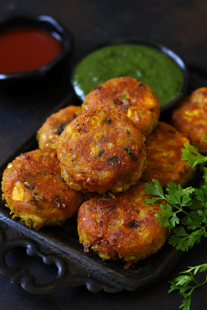Corn Paneer Cutlet in a Black Tray With Green Chutney Blur In The Background