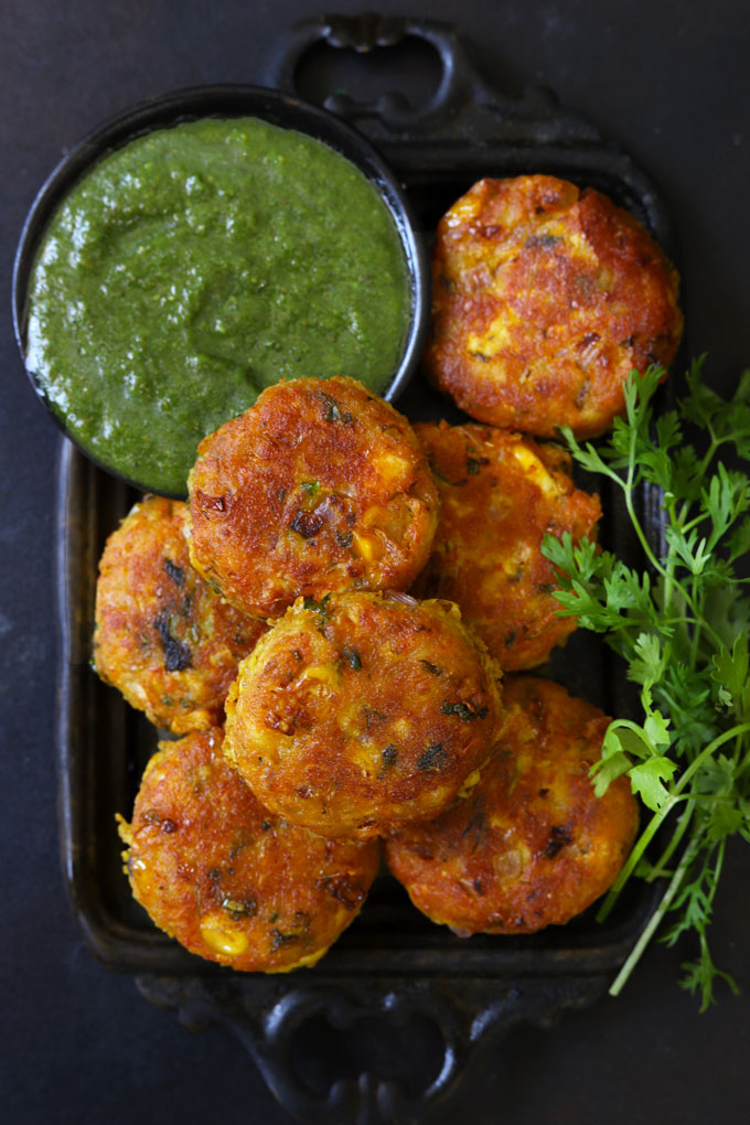 Aerial Shot of Corn Paneer Cutlet in a Black Tray With Green Chutney