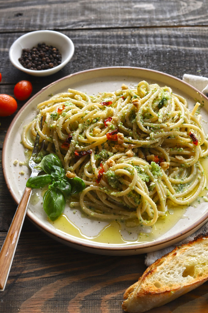 Side/aerial view of broccoli pesto pasta on wooden table with bread and tomatoes