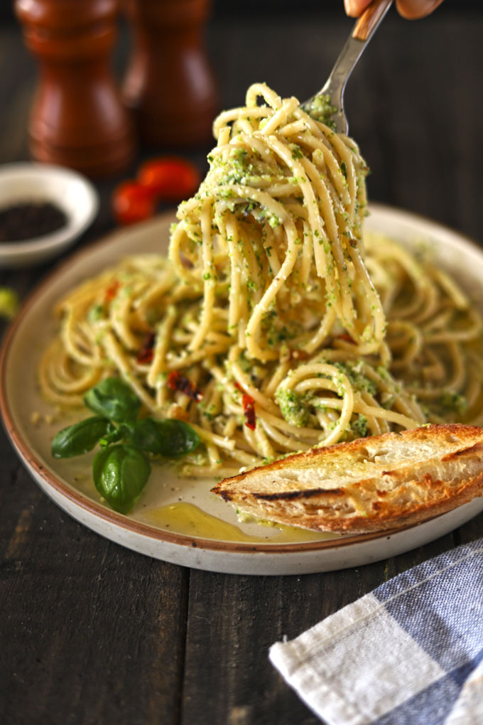Side view of broccoli pesto pasta being lifted off plate by fork on wooden table with bread on plate.