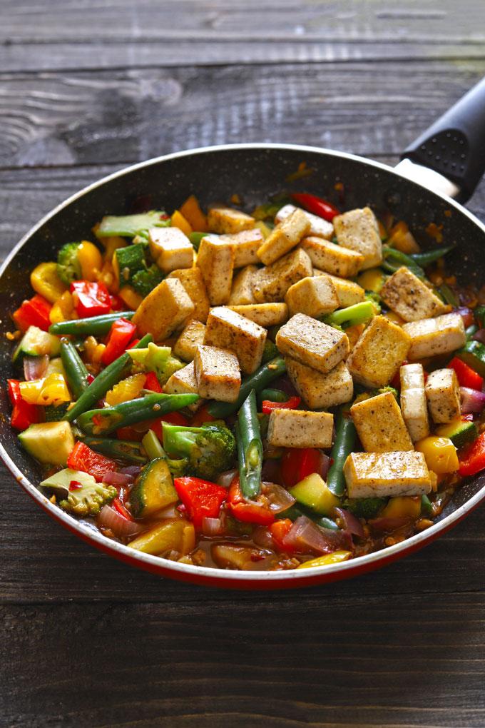 Vegan tofu stir fry in a frying pan on a dark wooden table.