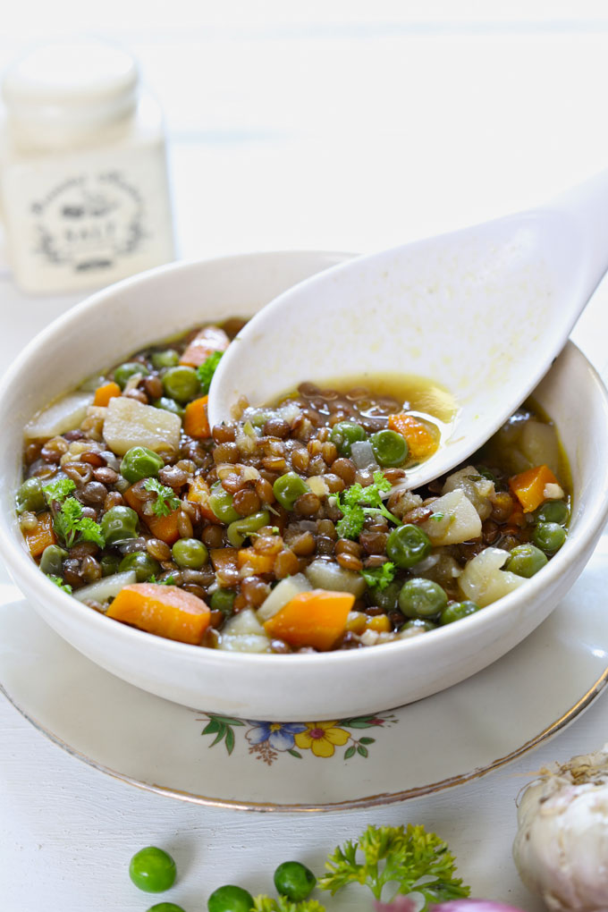 Lentil Stew in a white ceramic serving bowl with a serving spoon on a white background.
