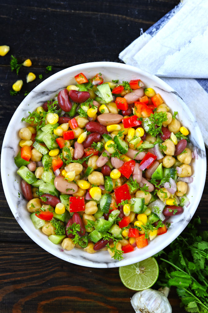 Aerial shot of Mexican style mixed beans salad in a white bowl.