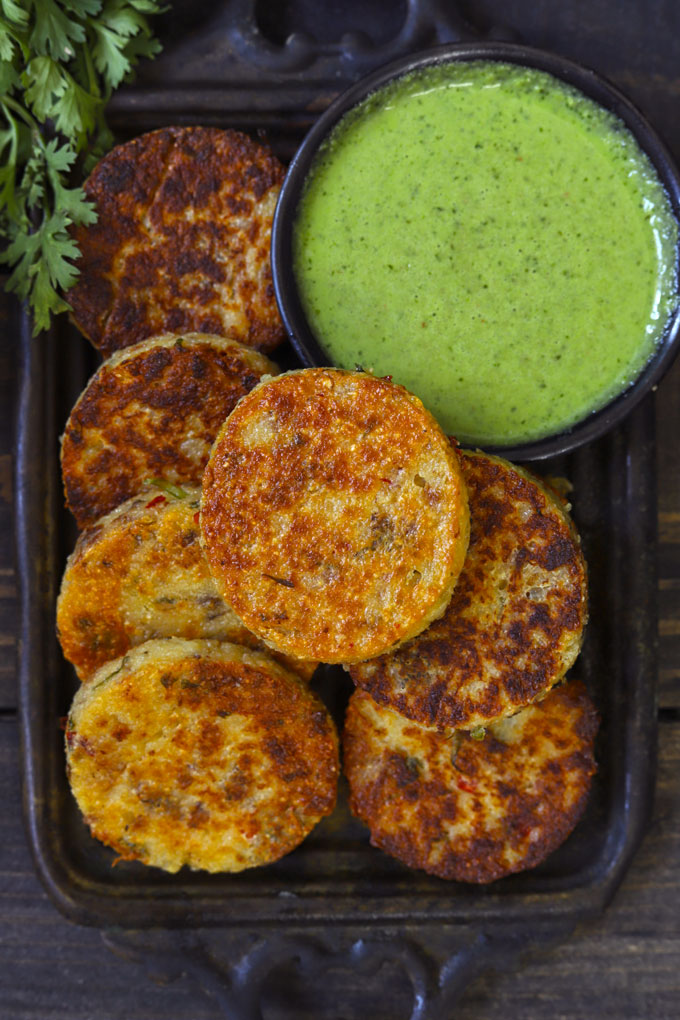 Aerial shot of suji cutlet in a black tray with green chutney on the side.