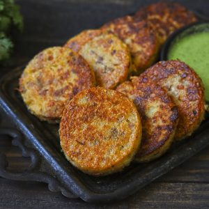 Suji Cutlet in a black tray with a green chutney.