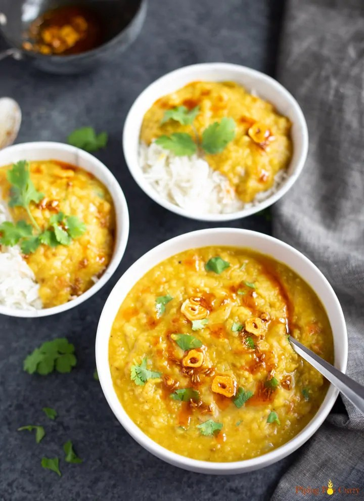 Red Lentil Curry with rice in serving bowls on a black surface