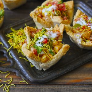 Side shot of bread basket chaat on a black tray.