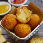 Side shot of stacked potato cheese balls in a frying basket.