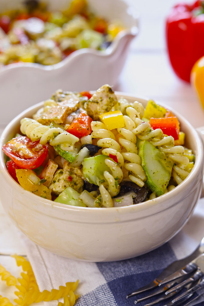 Side shot of pasta salad in a cream ceramic mug.