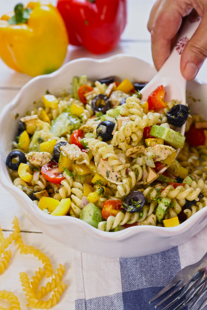 Side shot of mixing pasta salad in a white ceramic serving bowl