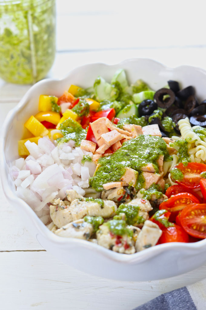 Side shot of pasta salad with herb dressing in a white ceramic bowl.