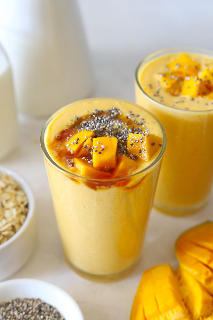 Side shot of mango oats breakfast smoothie in a glass.