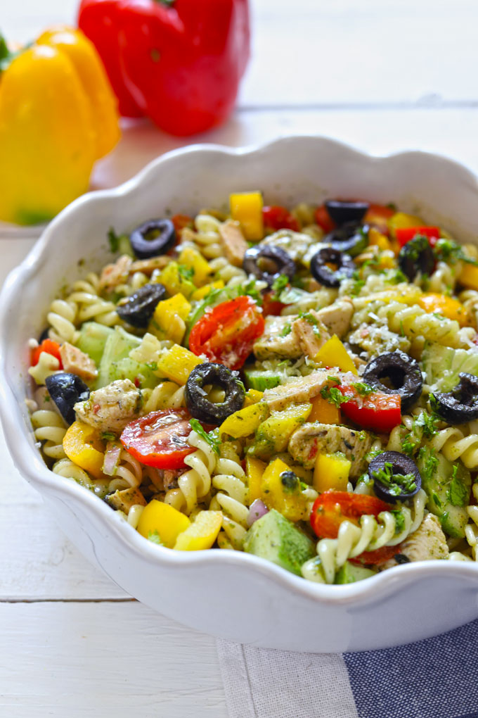 Side shot of chicken pasta salad in a white serving bowl.