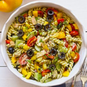 Aerial shot of chicken pasta salad in a white ceramic serving bowl.