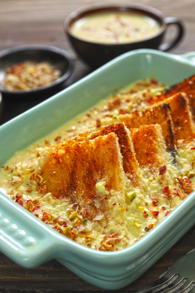 Side shot of baked shahi tukra in a green ceramic baking dish.