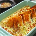 Side shot of baked shahi tukra in a green ceramic baking dish.