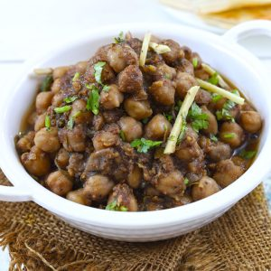 Side shot of chana masala in a white serving bowl