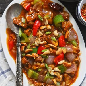 aerial shot of chilli mushroom in a white ceramic platter with a silver spoon