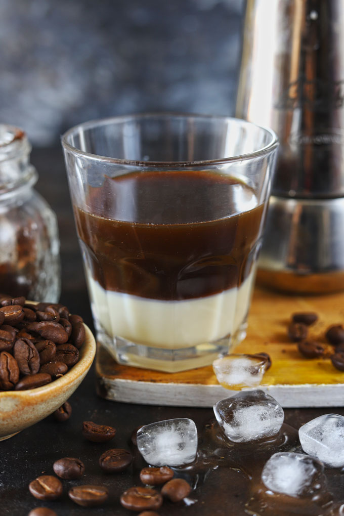 Side shot of condensed milk and brewed coffee in a glass.
