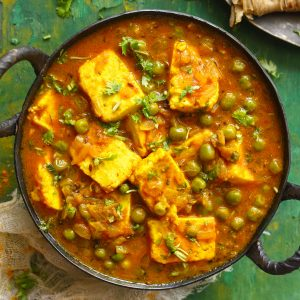 aerial shot of Indian matar paneer curry in a cast iron skillet