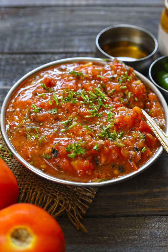 side shot of roasted tomato chutney in a steel bowl with a spoon