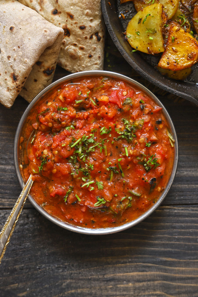 aerial shot of roasted tomato chutney in a steel bowl with a spoon