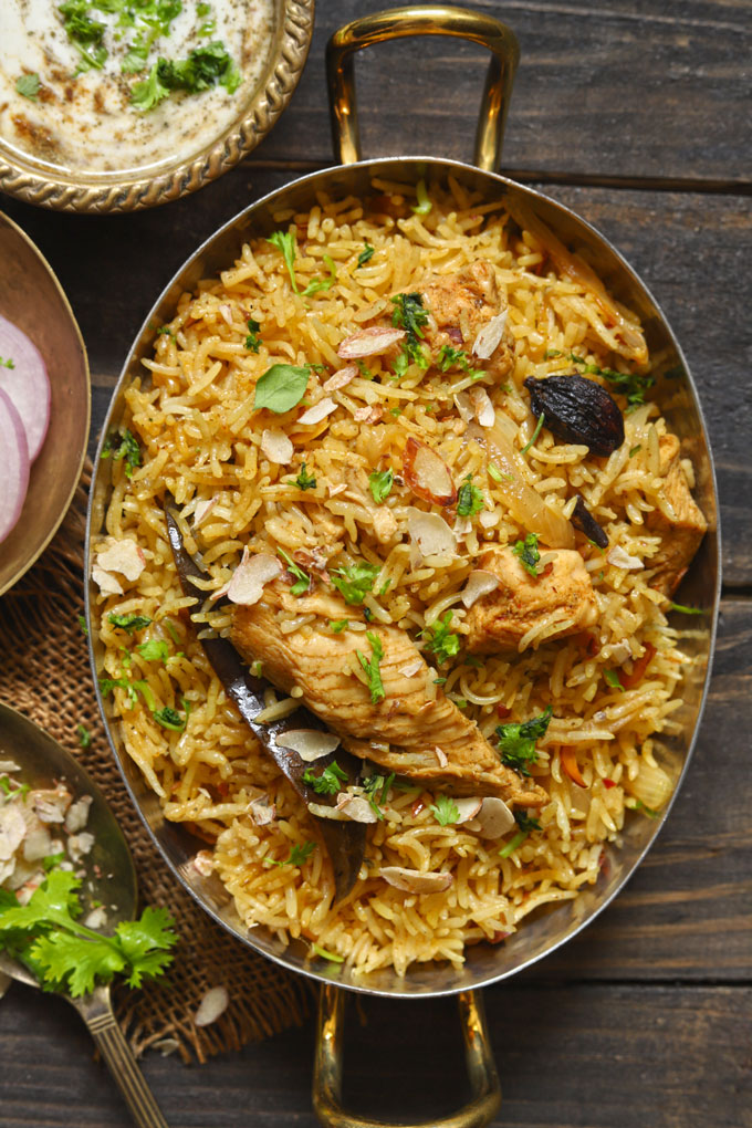 aerial shot of chicken pulao in an oval brass serving bowl