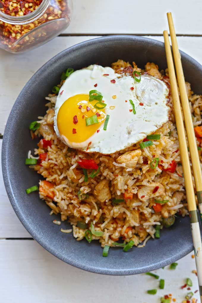 aerial shot of fried rice topped with half fried egg in a black ceramic bowl with chopsticks