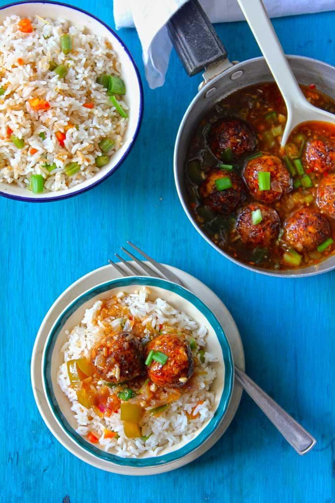 aerial shot of manchurian balls gravy over fried rice in a white bowl