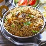 side shot of mushroom pulao in a copper serving bowl