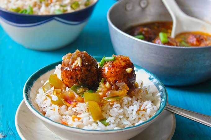 side shot of vegetable manchurian balls over fried rice in a white bowl