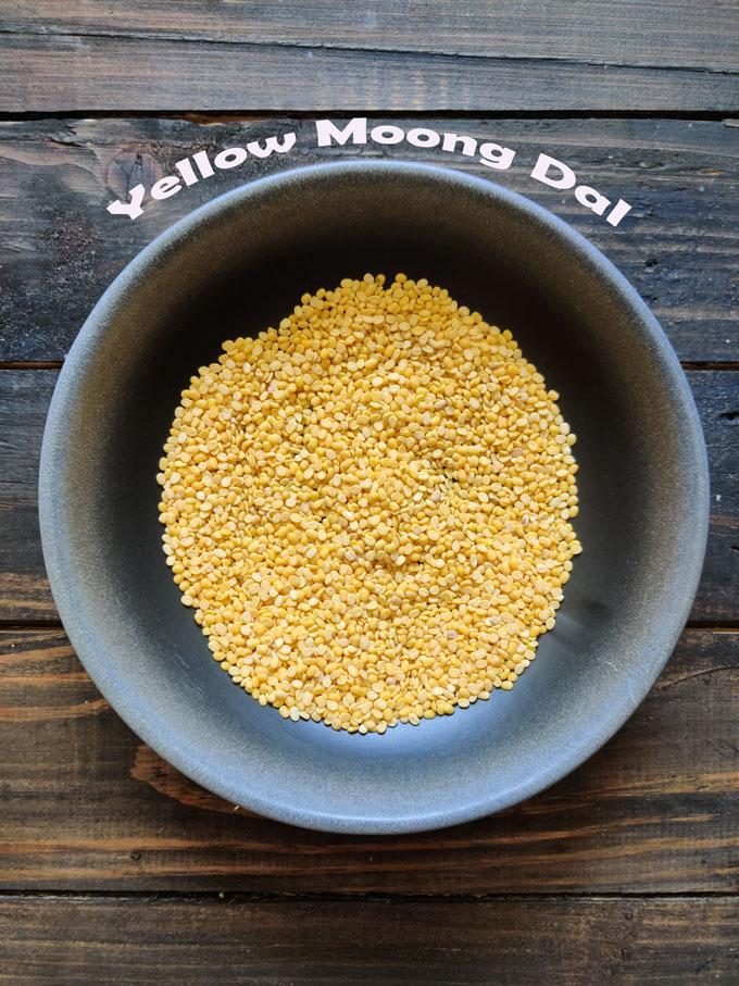 aerial shot of yellow moong dal in a black ceramic bowl