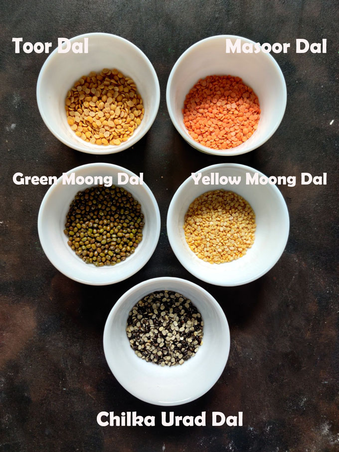 aerial shot of five lentils in bowls on a black surface